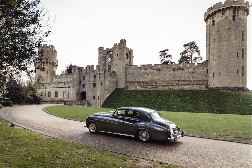 Black car pulling up the path leading to a castle