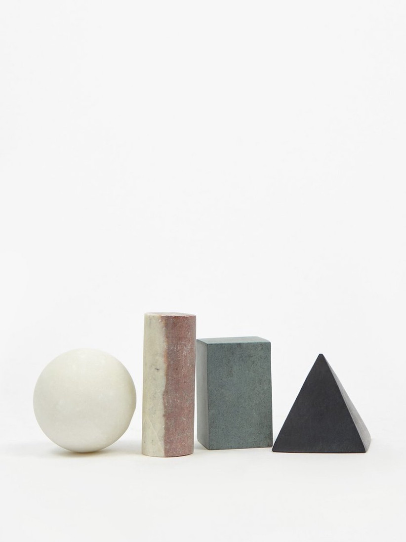 Four different shaped sculptural whiskey stones in natural stone shades