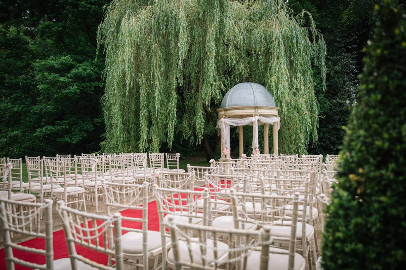 Outside wedding ceremony under a weeping willow with a stone pavilion