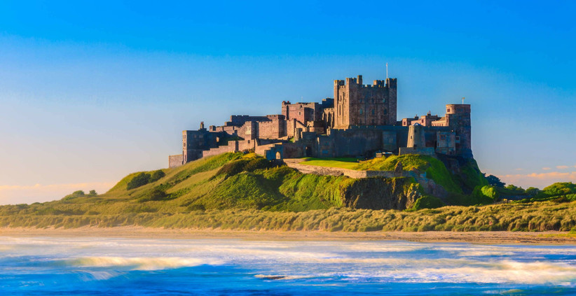 Bamburgh Castle on a green hill overlooking the sea