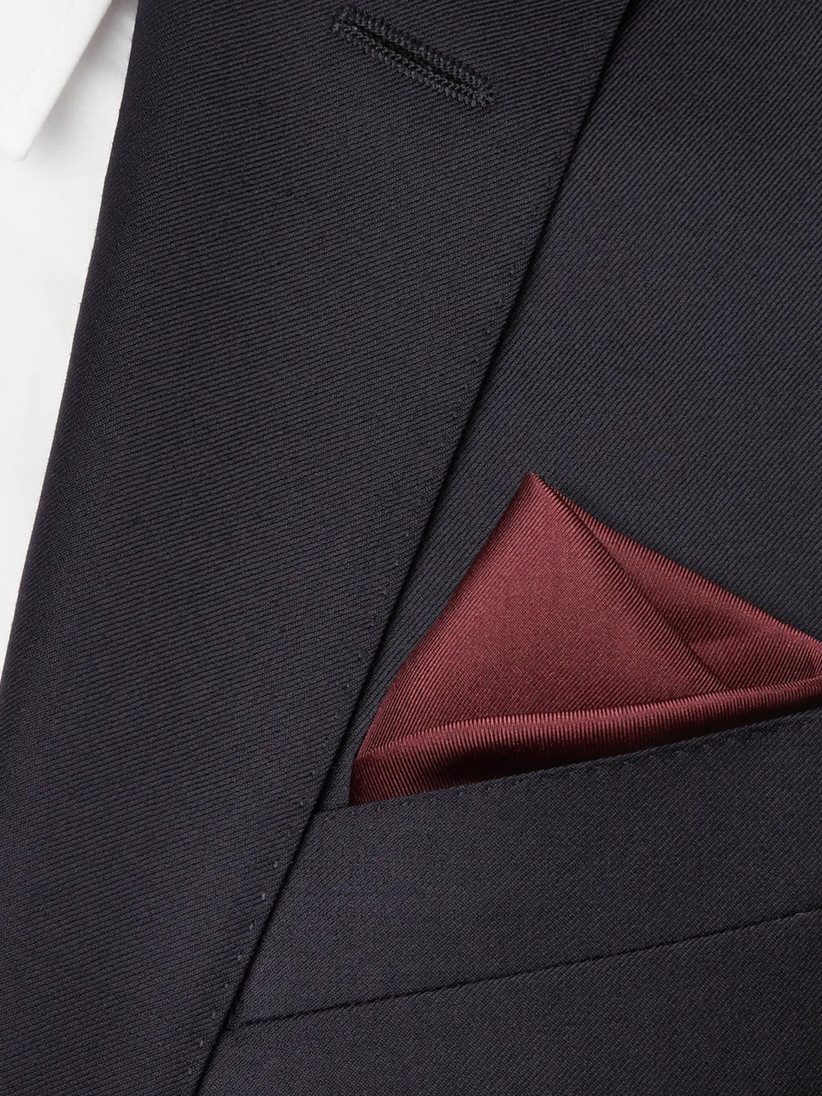 Close up of a dark grey suit with a burgundy silk pocket square