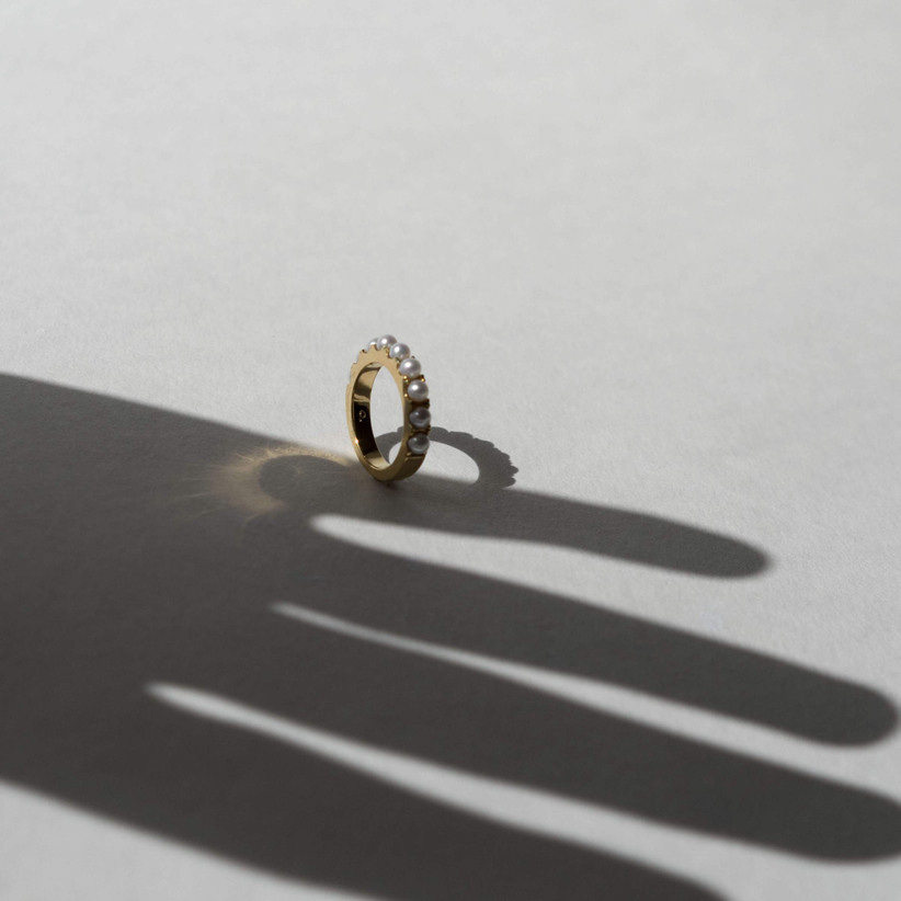 A gold pinky ring crowned with a row of pearls balanced on its side against a white background