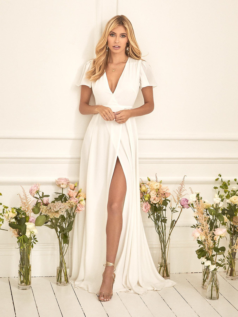 Girl in a white wedding dress with leg split surrounded by vases of flowers