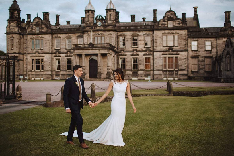 Bride and groom holding hands outside a country house