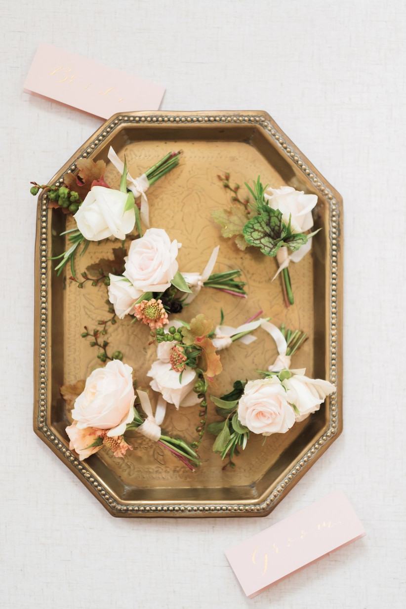 A tray full of pink rose buttonholes