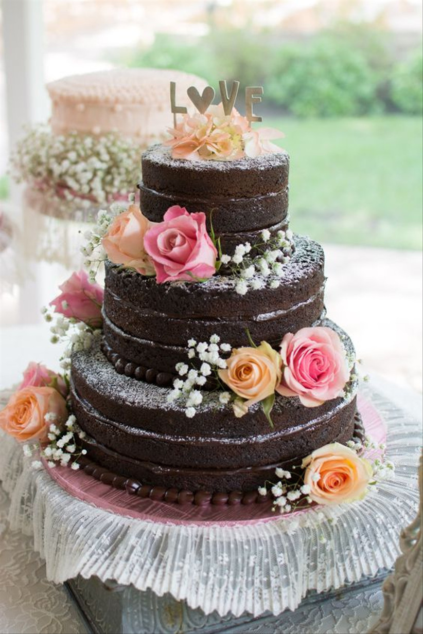 Three tiered naked chocolate rustic wedding cake with flowers
