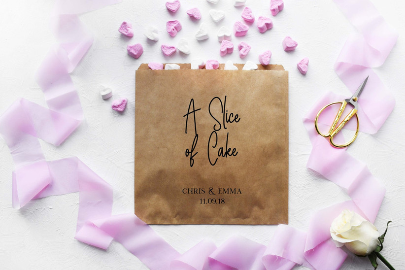A slice of cake brown paper bag surrounded by rose petals and ribbon