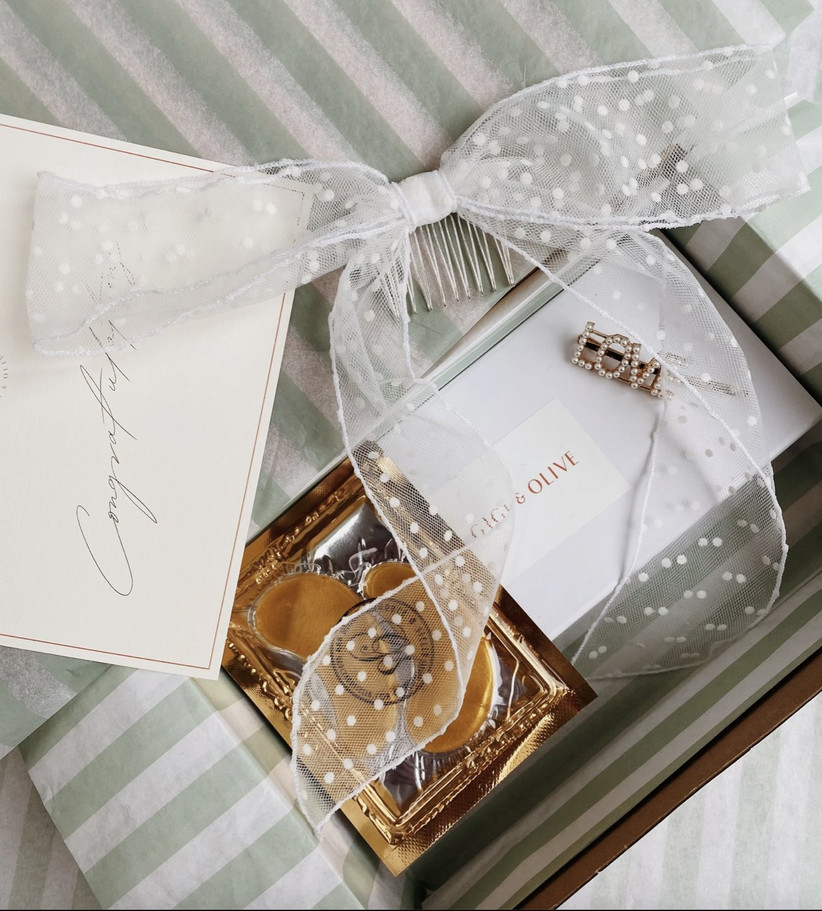 White and green striped gift box filled with a sheer polka dot ribbon, LOVE pearl hair clip, golden under eye masks and a handwritten note