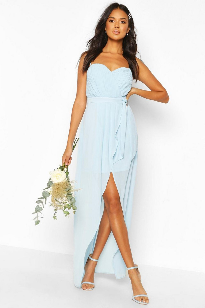 Girl wearing a bandeau blue maxi dress, holding a bouquet