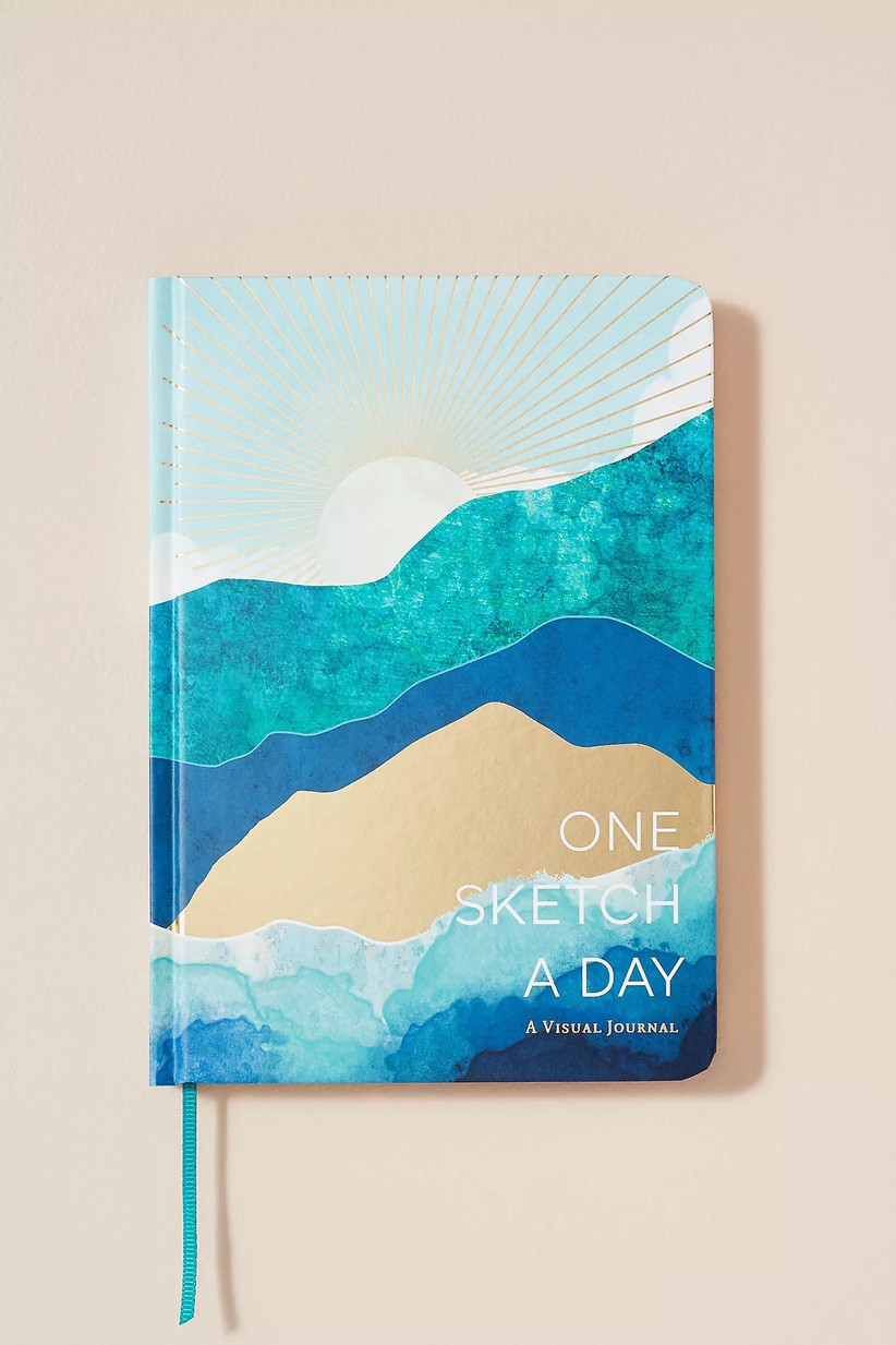 A one sketch a day visual journal with a sun and sea scene painted on the cover