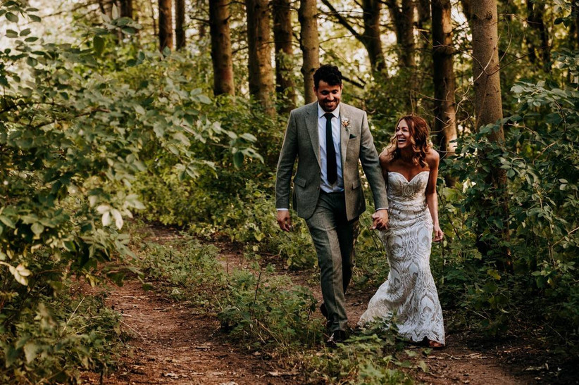 Bride and groom walk hand and hand in the woods