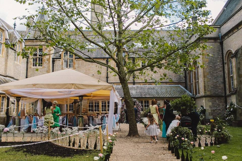 Wedding guests mingling outside a castle with a gazebo