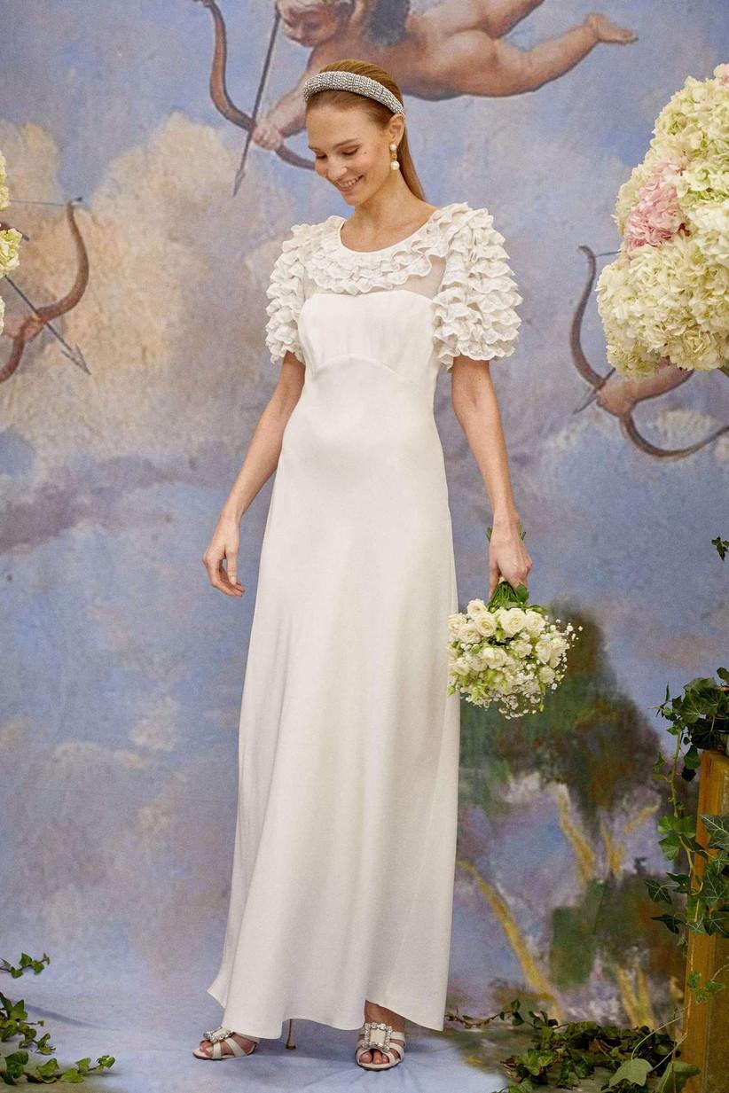 Girl wearing a ruffled white wedding dress holding a white bouquet