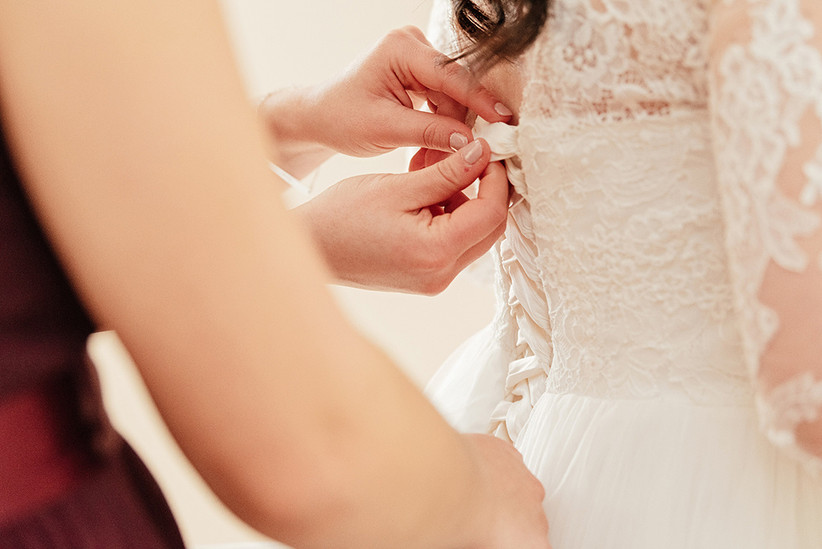Hands lacing up the back of Becky's white wedding dress