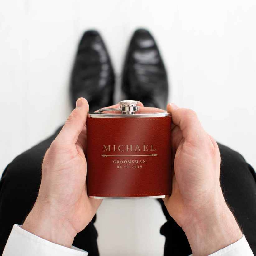 A man in a suit holding a personalised brown hipflask in both hands