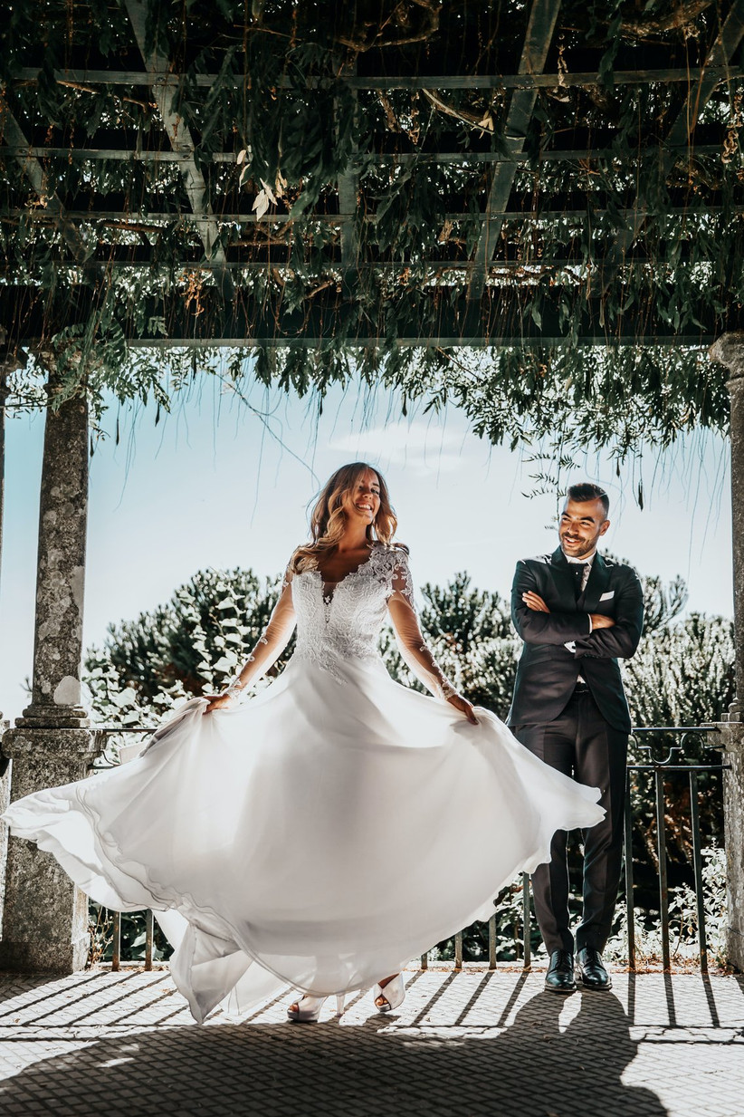 Laughing bride twirling her wedding dress while groom looks on laughing
