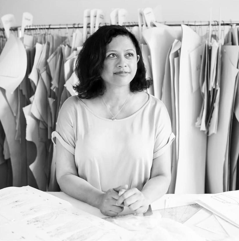 Bridal designer Sabina Ali at work in her studio with a rack of wedding dresses behind her