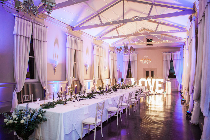 Wedding reception room with candles, fairy lights and a light-up love sign