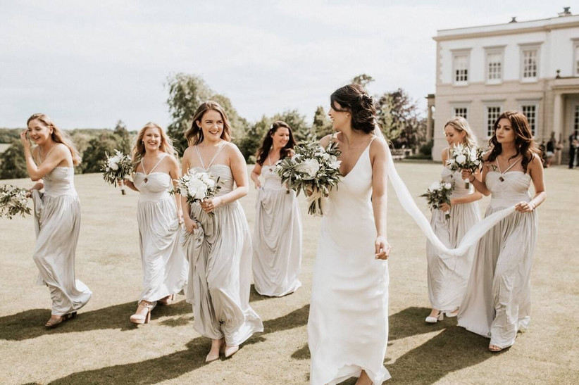 Bride walks with her bridesmaids outside a country wedding venue