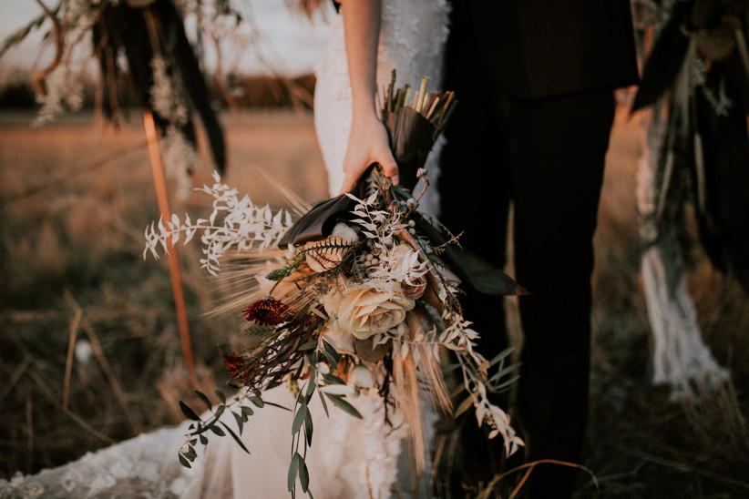 Wedding couple in field holding rustic flower bouquet