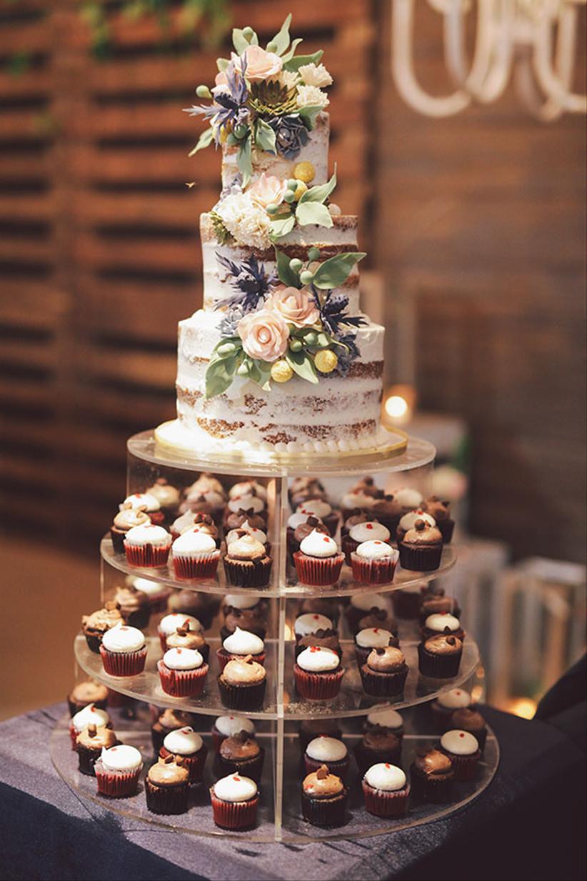 Three tiered semi naked rustic wedding cake with mini cupcake display