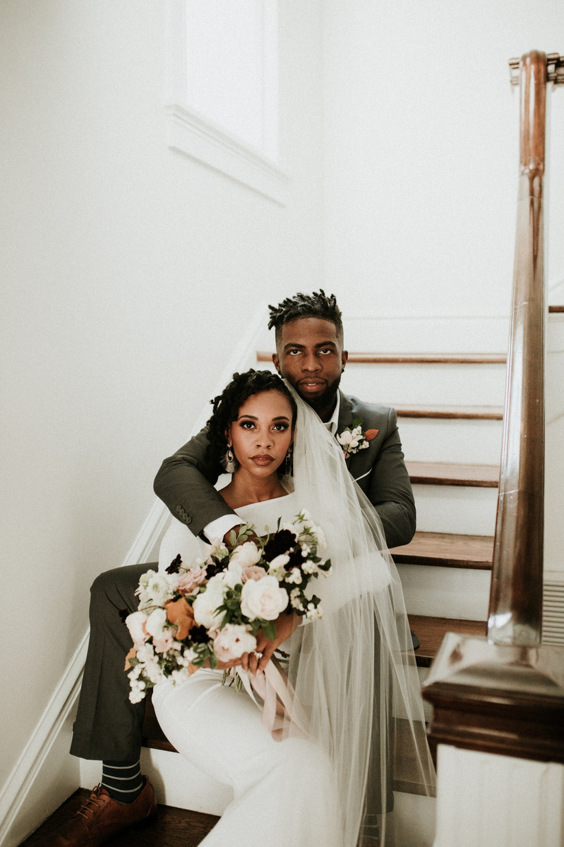 Black bride and groom sitting on stairs in wedding outfits