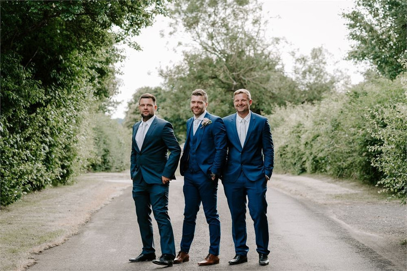 Three groomsmen in blue suits standing in a line outside