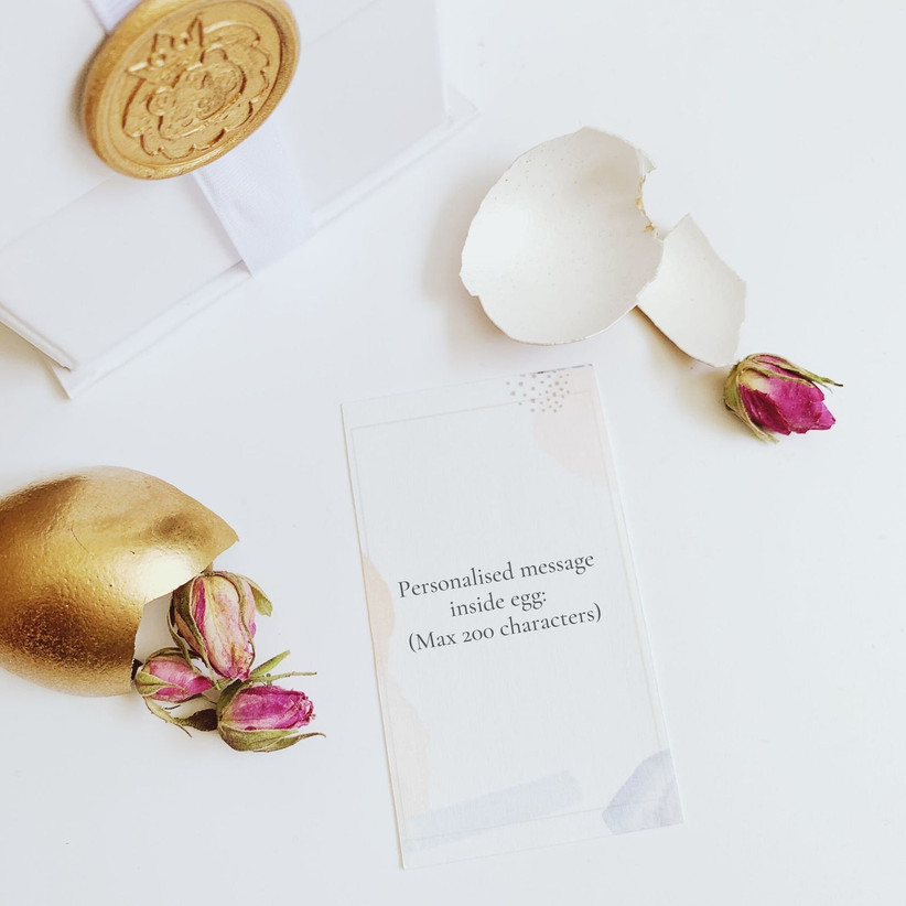 Gold egg cracked open with a personalised note and pink roses inside next to a white gift box with a gold ribbon