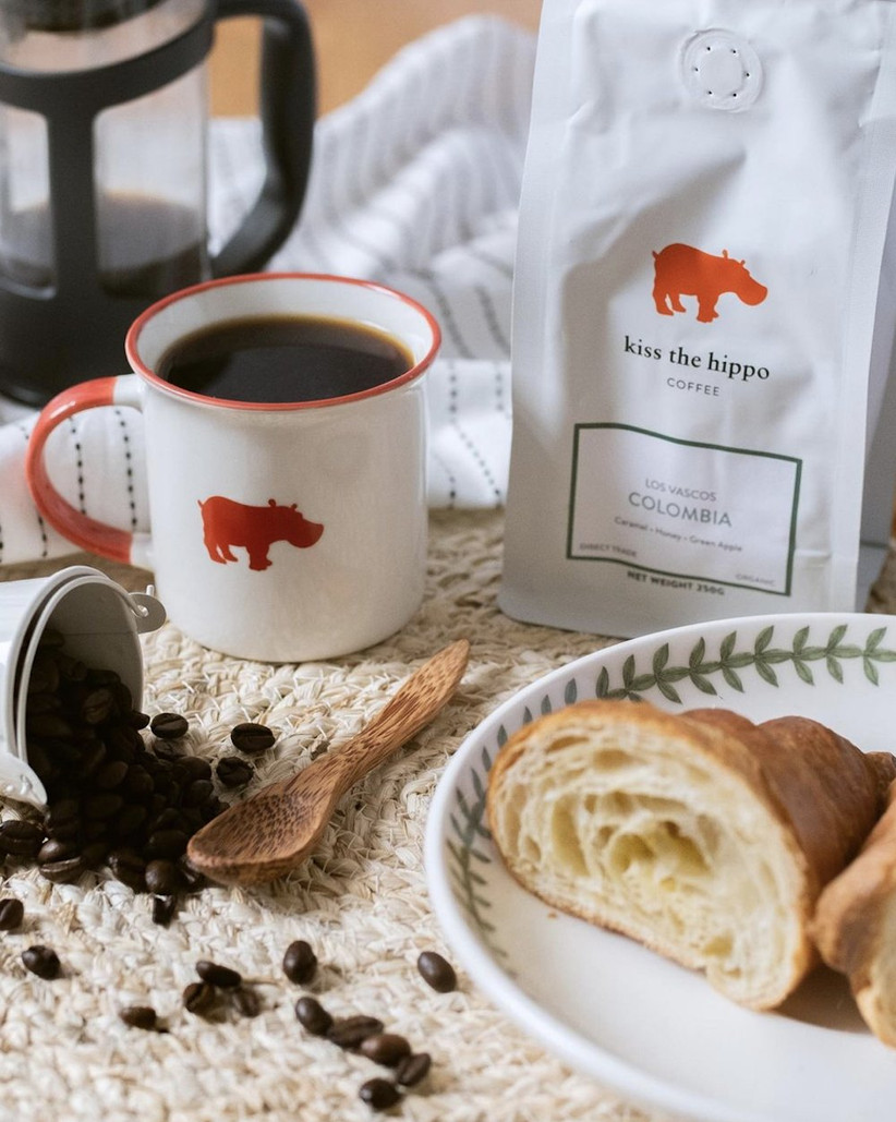 Breakfast table with a tub of coffee beans spilling onto a mat, an enamel coffee cup decorated with a red hippo, a bag of Colombian coffee and a croissant on a white plate decorated with green leaves