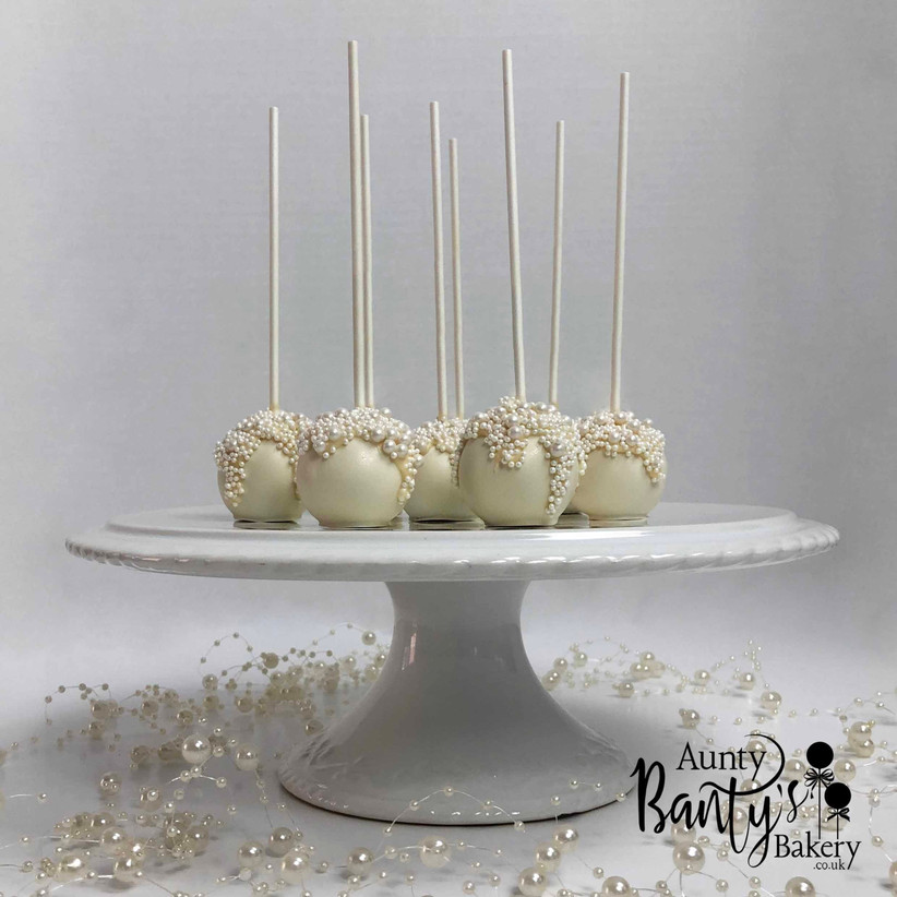 White and pearl cake pops on a cake stand