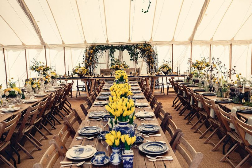 Wedding dining area in a marquee with wooden tables and yellow tulips