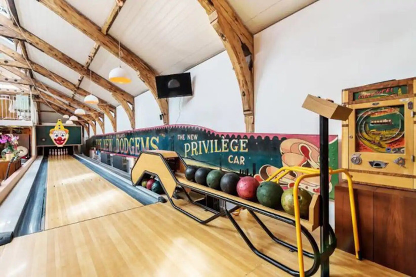 Bowling alley in a room with rustic wooden beams and clown sign