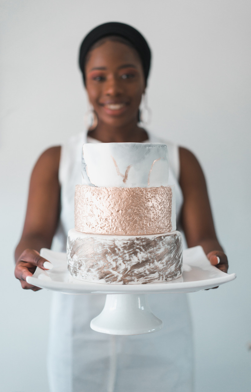 Woman holding three tier wedding cake