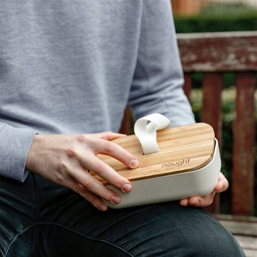 man holding a bamboo lunch box