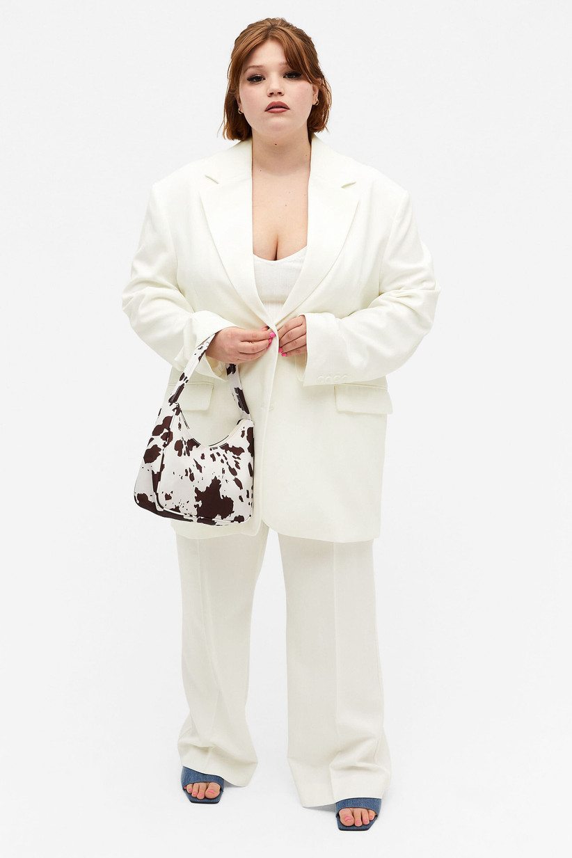 Girl wearing a white suit with a cow print bag and blue heels