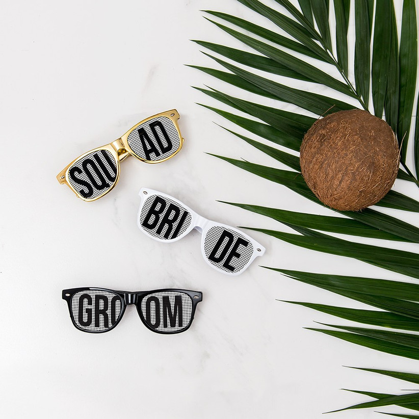 Three pairs of personalised sunglasses next to a palm leaf and a coconut