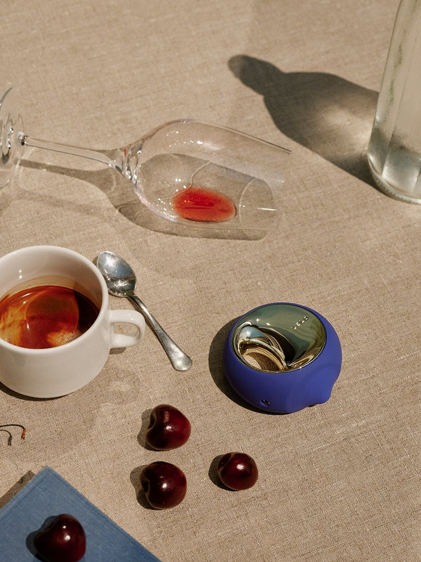 Royal blue circular sex toy with a gold top on a linen table cloth with loose cherries, an empty wine glass and a coffee cup