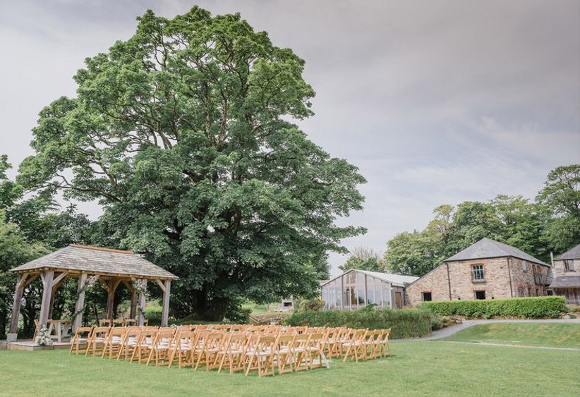 Outside wedding ceremony with wooden gazebo and chairs