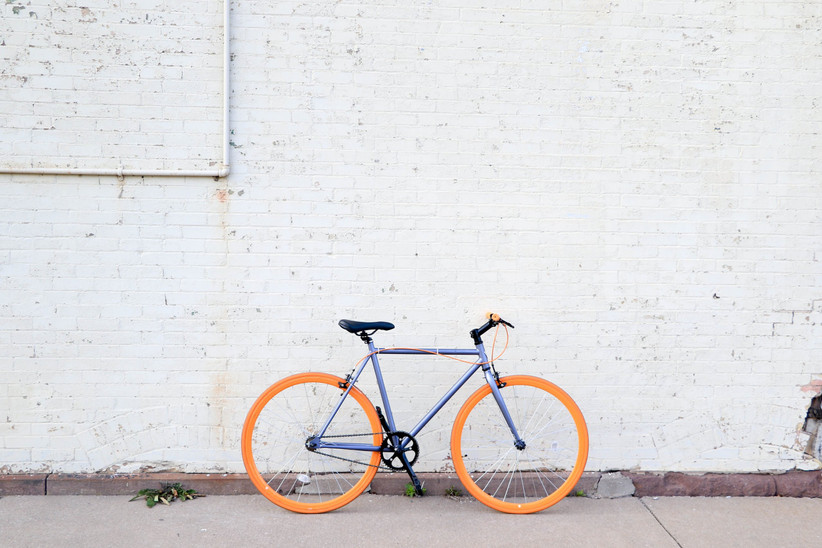 A blue bike with bright yellow wheels parked up against a white brick wall