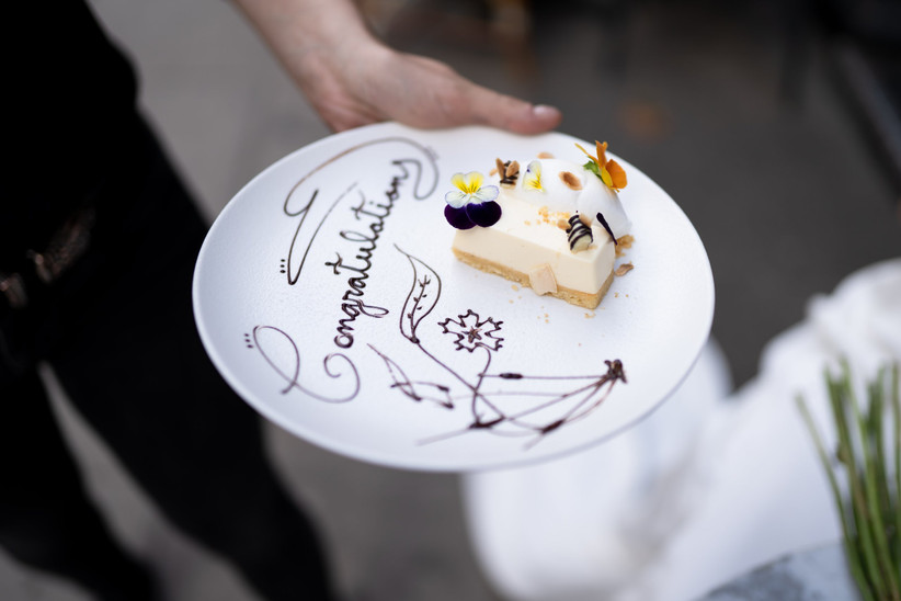 A piece of cake on a plate with congratulations written on it