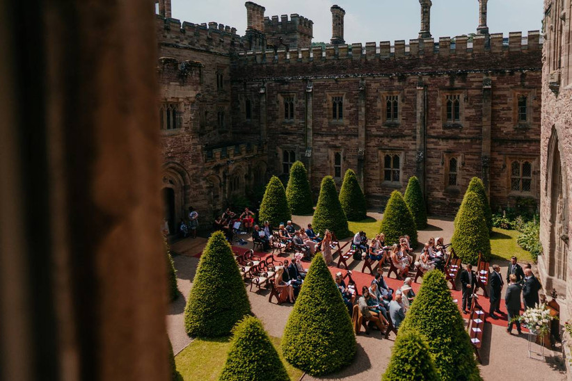 Outside ceremony at a castle with manicured trees