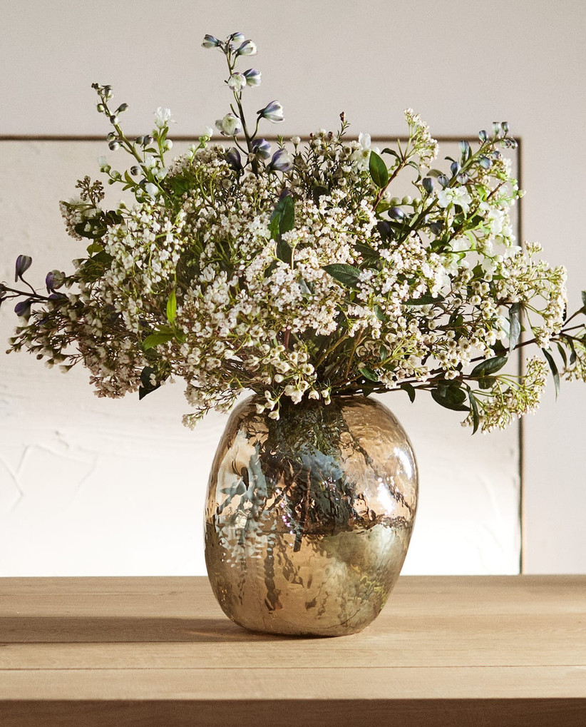 Irregular shaped dappled golden glass vase on a wooden table containing white wild flowers and foliage