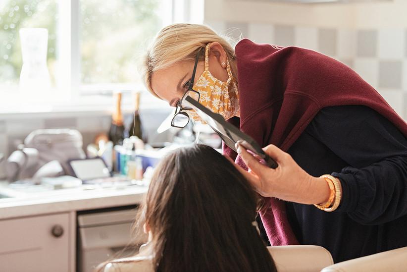 Hairdresser in a mask holding up a mirror to Becky