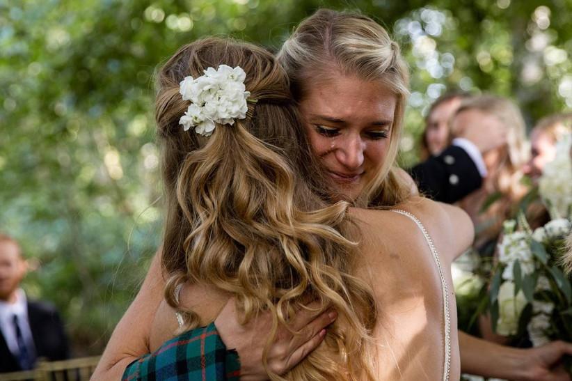 Bridesmaid hugging an emotional bride