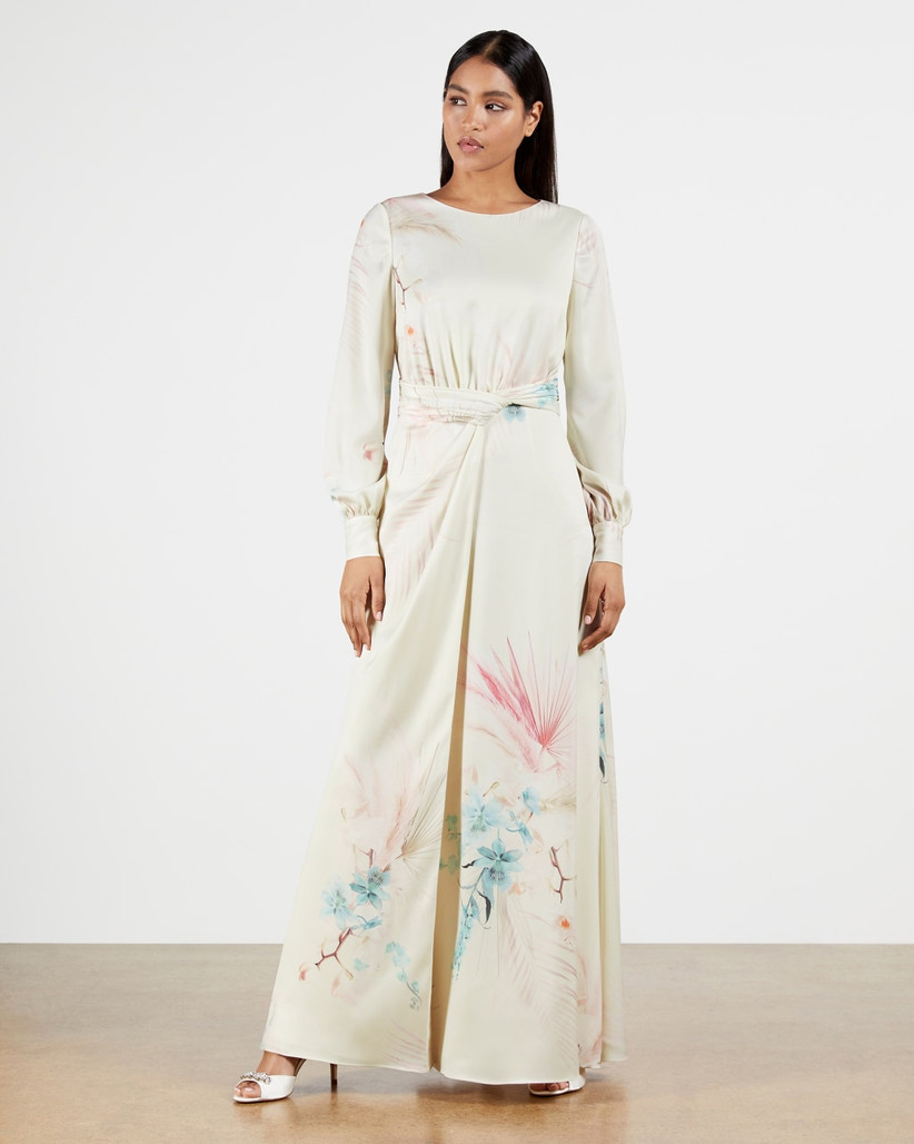 White maxi dress with long sleeves and pastel pattern on skirt