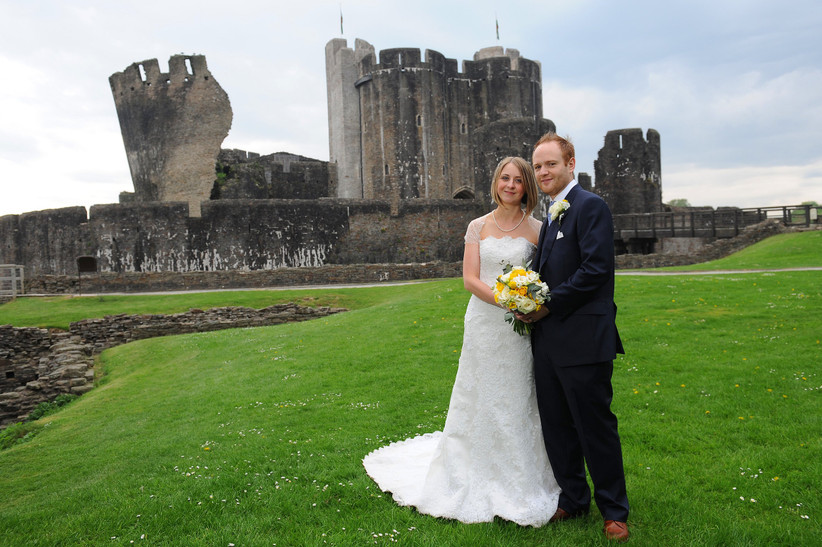 Bride in a cap sleeved white wedding dress with blonde bob holding a yellow and white bouquet next to a grim in a navy suit smiling in front on Caerphilly Castle