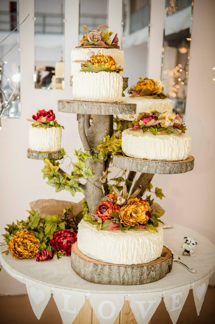 Six individual textured rustic wedding cakes with autumnal flowers