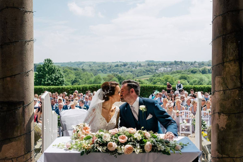 Bride and groom kiss at an outside wedding ceremony