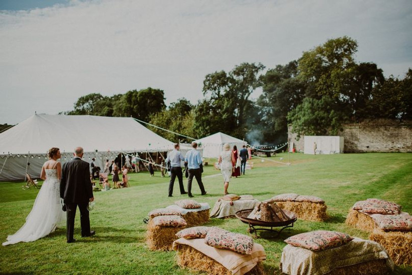 Wedding guests outside gazebos with rustic hay bale seats