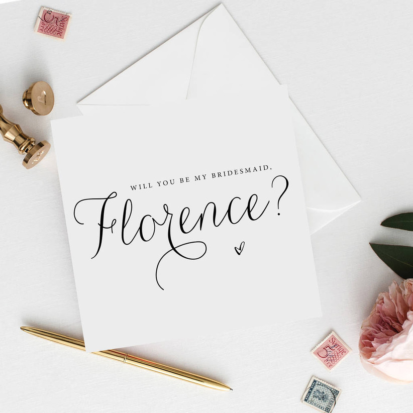 White card with loopy black calligraphy reading will you be my bridesmaid Florence
